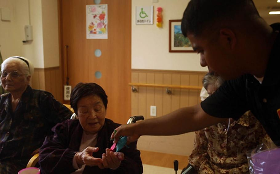 Marine Staff Sgt. Ismael Esconde passes out paper cranes to the residents of the Pay Nursing Home Fuga in Kin, Okinawa, on Nov. 25, 2016.