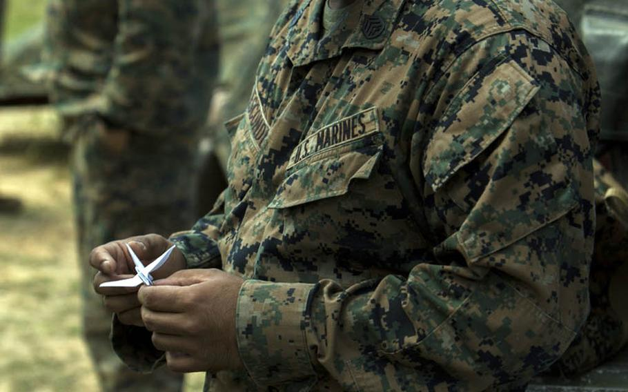 Staff Sgt. Ismael Esconde folds a paper crane during his free time in the field at Landing Zone Dodo, Okinawa, Nov. 2, 2016.