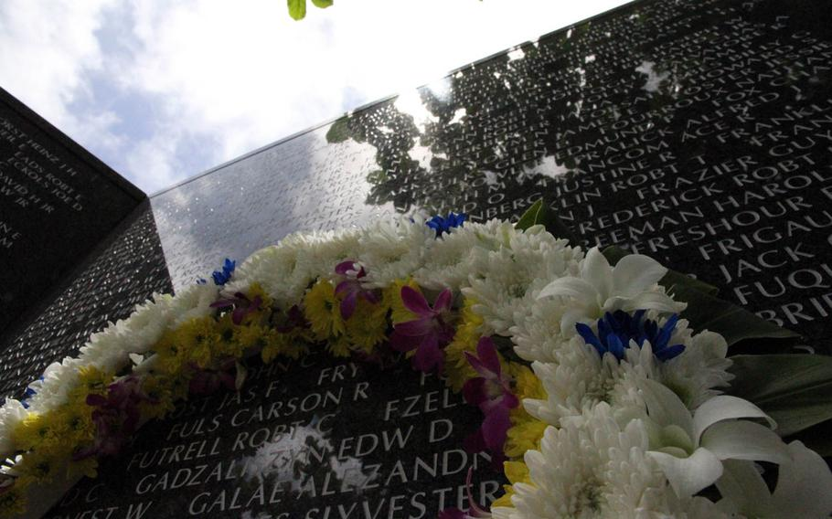 A wreath rests against the names of some of the thousands of Americans inscribed at Okinawa Peace Memorial Park in Naha, Friday, June 23, 2017.