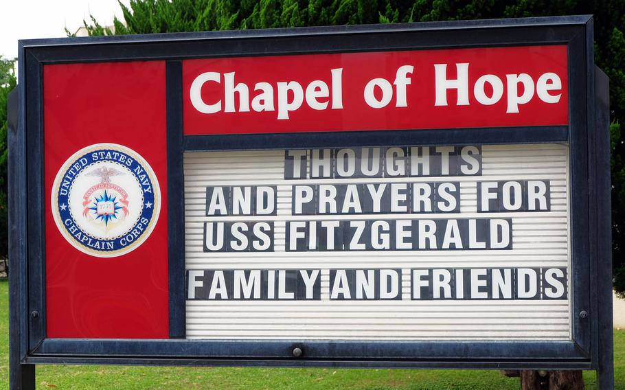 A sign at the Yokosuka Naval Base Chapel encourages thoughts and prayers for USS Fitzgerald sailors and their families, Tuesday, June 27, 2017.