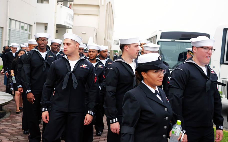 Sailors board buses to attend a memorial service for seven USS Fitzgerald sailors at Yokosuka Naval Base, Japan, Tuesday, June 27, 2017.