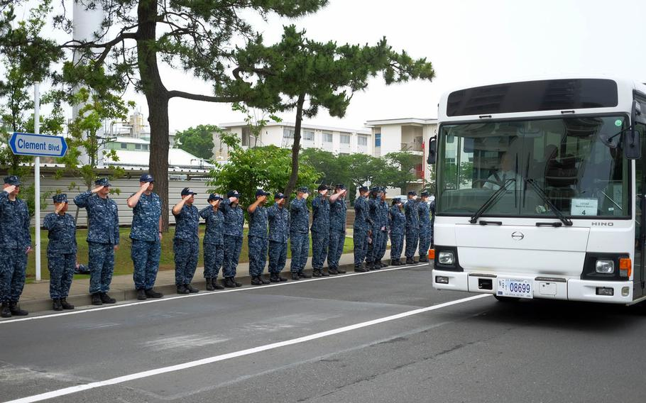 Servicemembers salute a procession of USS Fitzgerald sailors and their families ahead of a memorial ceremony at Yokosuka Naval Base, Japan, Tuesday, June 27, 2017.