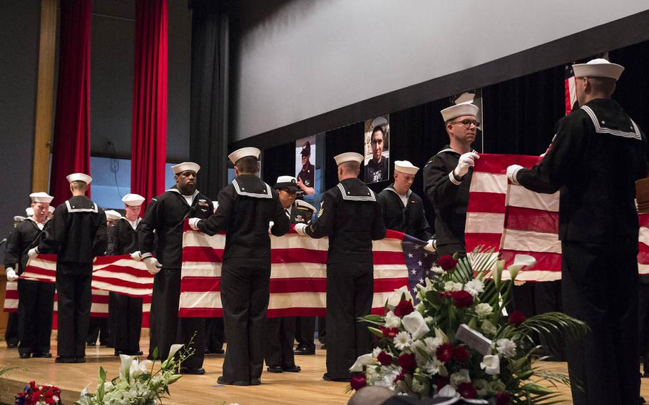 Sailors ceremonially fold seven American flags during a memorial ceremony for seven USS Fitzgerald sailors at Yokosuka Naval Base, Japan, Tuesday, June 27, 2017.