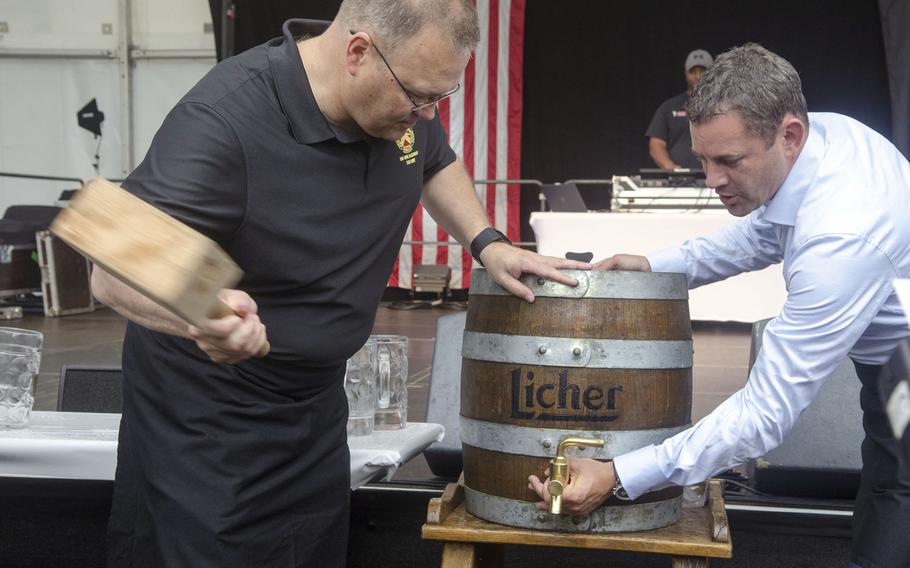 Col. Todd Fish, left, commander of U.S. Army Garrison Wiesbaden, uses a wooden hammer to tap a keg of beer, aided by Wiesbaden mayor Sven Gerich, Thursday, June 29, 2017 in Wiesbaden, Germany. The tapping of the keg was the ceremonial start to the six-day German-American Friendship Fest, which will culminate with fireworks the night of July 4.
