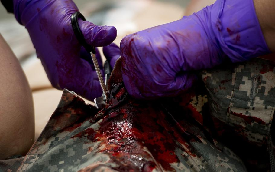 Staff Sgt. Chelsea Rittenhouse cuts the clothes off a simulated casualty to expose a wound during a mass casualty exercise at Ramstein Air Base, Germany, on Thursday, June 29, 2017.