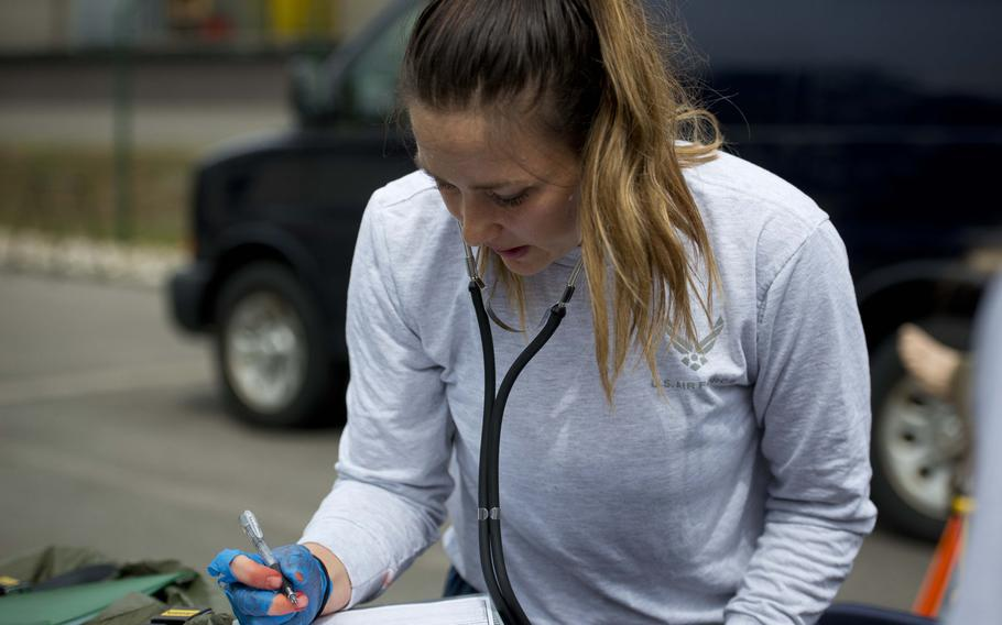 Staff Sgt. Jozlinn Rae annotates a simulated casualty's vitals during a mass casualty exercise at Ramstein Air Base, Germany, on Thursday, June 29, 2017.