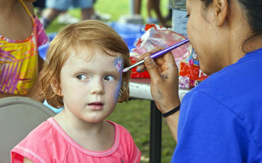 A girl tries hard to stay still as a volunteer paints her face during the Celebrate America festival at Yokota Air Base, Japan, Friday, June 30, 2017.