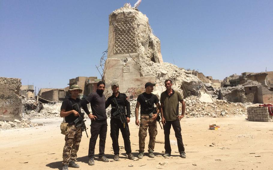 Iraqi troops at the base of al-Hadba, Mosul's famous leaning minaret, on Thursday, July 20, 2017. The minaret and the Great Mosque of al-Nuri were blown up by the Islamic State group last month.