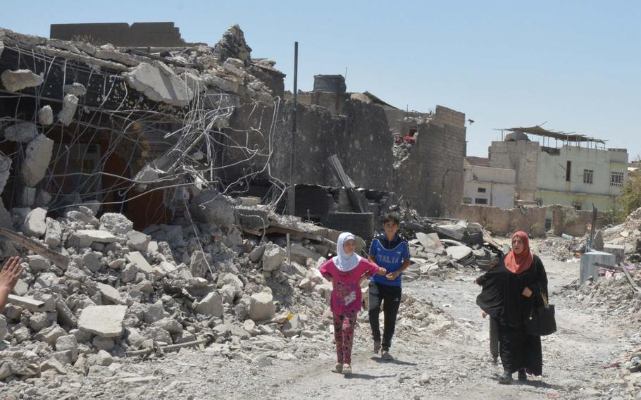 A family searches for what's left of their home near the ruins of the Great Mosque of al-Nuri in Mosul's Old City on Thursday, July 20, 2017.