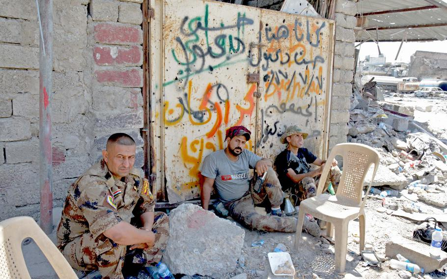 Iraqi troops wait in the shade near the ruins of the Great Mosque of al-Nuri in Mosul's Old City on Thursday, July 20, 2017.