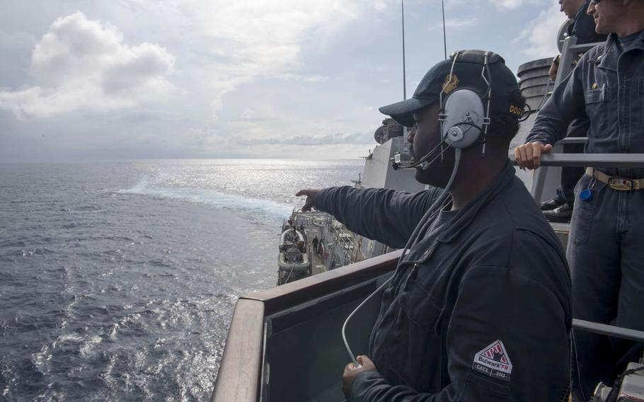 Seaman Dorsey Cadette, left, of the guided-missile destroyer USS Stethem, points out a smoke signal during man-overboard training in the South China Sea, July 10, 2017.