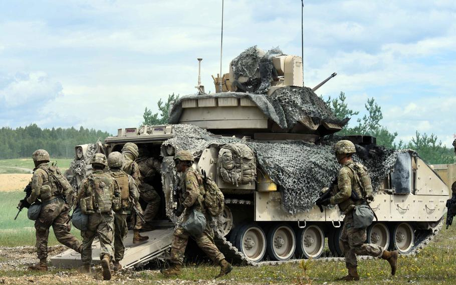Soldiers with the Army's 1st Battalion, 68th Armored Regiment, pile into the back of a Bradley Fighting Vehicle during a live fire exercise in Grafenwoehr, Germany, Friday, Aug. 4, 2017.