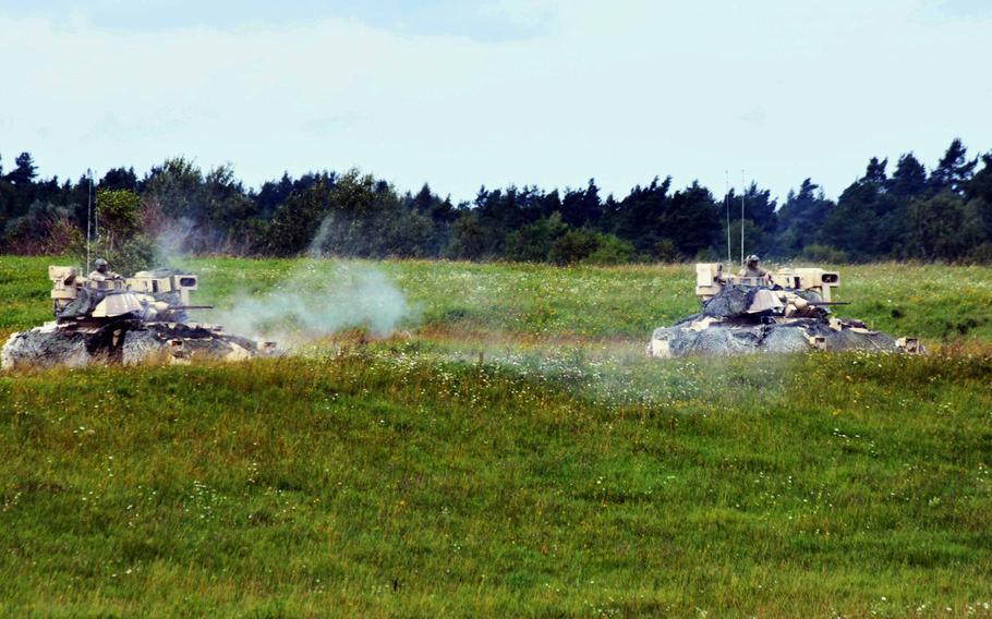 Bradley Fighting Vehicles with the Army's 1st Battalion, 68th Armored Regiment, fire their machine guns during a live fire exercise in Grafenwoehr, Germany, Friday, Aug. 4, 2017.