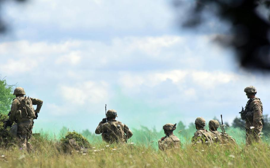 Soldiers with the Army's 1st Battalion, 68th Armored Regiment radio their command after securing an area during a live-fire exercise in Grafenwoehr, Germany, Friday, Aug. 4, 2017.