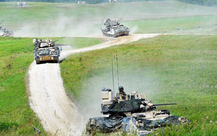 Bradley Fighting Vehicles maneuver to an extraction point to bring their dismounted soldiers away from the front lines during a live-fire exercise in Grafenwoehr, Germany, Friday, Aug. 4, 2017.