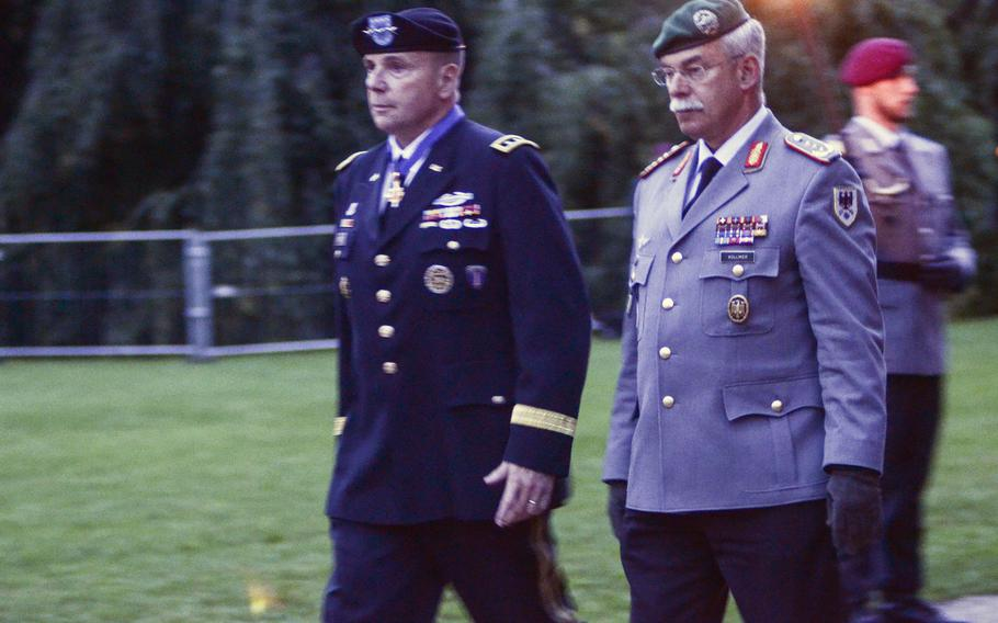 Lt. Gen. Ben Hodges, commander of U.S. Army Europe, and Bundeswehr Chief of Staff Lt. Gen. Joerg Vollmer walk to their seats at a farewell playing of the Grosser Zapfenstreich, or Grand Tattoo, for Hodges, Thursday, Aug. 10, 2017 in Wiesbaden, Germany.