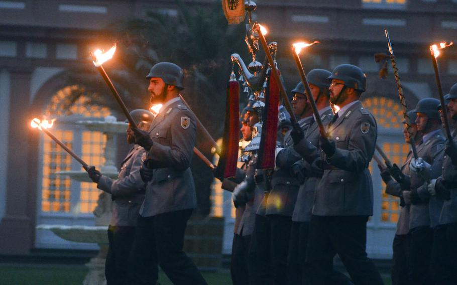 Bundeswehr soldiers carry torches as they march toward their positions at a Grosser Zapfenstreich, or Grand Tattoo, Thursday, Aug. 10, 2017 at Biebrich Palace in Wiesbaden, Germany.