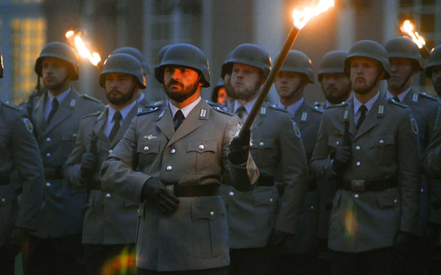 Bundeswehr soldiers carry torches as they march toward their positions at a Grosser Zapfenstreich, or Grand Tattoo, Thursday, Aug. 10 at Biebrich Palace in Wiesbaden, Germany.
