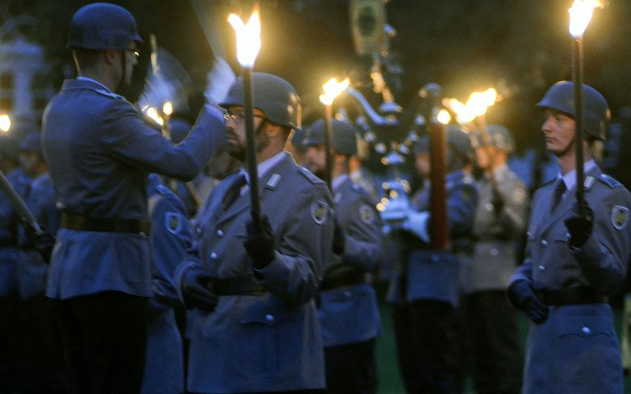 The conductor of the German army band from Ulm directs his charges during a Grosser Zapfenstreich, or Grand Tattoo, Thursday, Aug. 10, 2017 at Biebrich Palace in Wiesbaden, Germany.