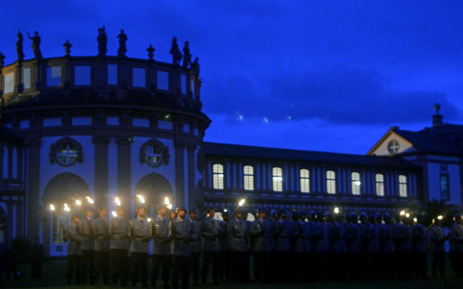 Bundeswehr soldiers stand during the playing of the Grosser Zapfenstreich, or Grand Tattoo, Thursday, Aug. 10, 2017 at Biebrich Palace in Wiesbaden, Germany. The palace, built in the early 18th century, has been the site of the past three tattoos — solemn evening military band performances — bidding farewell to leaders of U.S. Army Europe.