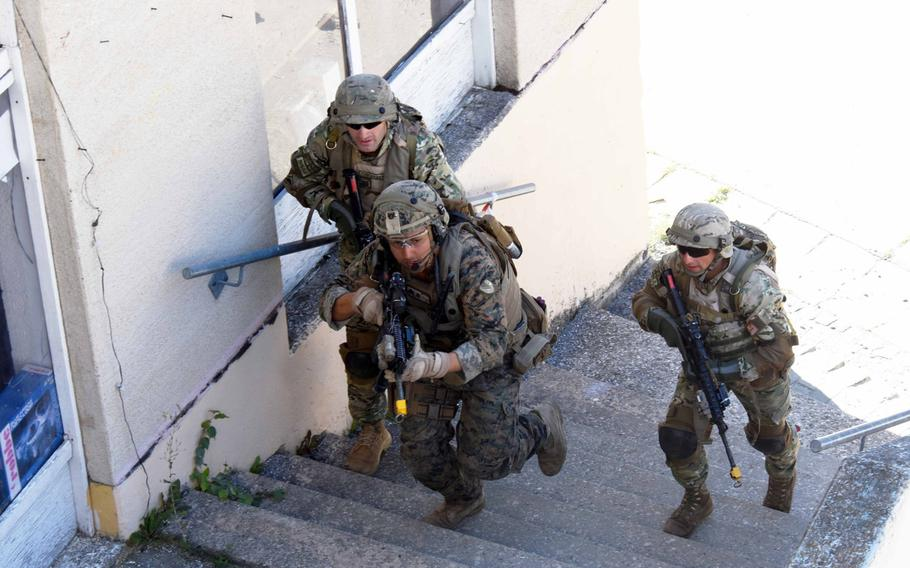 Georgian soldiers and a U.S. Marine run toward a hostile threat during training in Hohenfels, Germany, Tuesday, August 15, 2017.