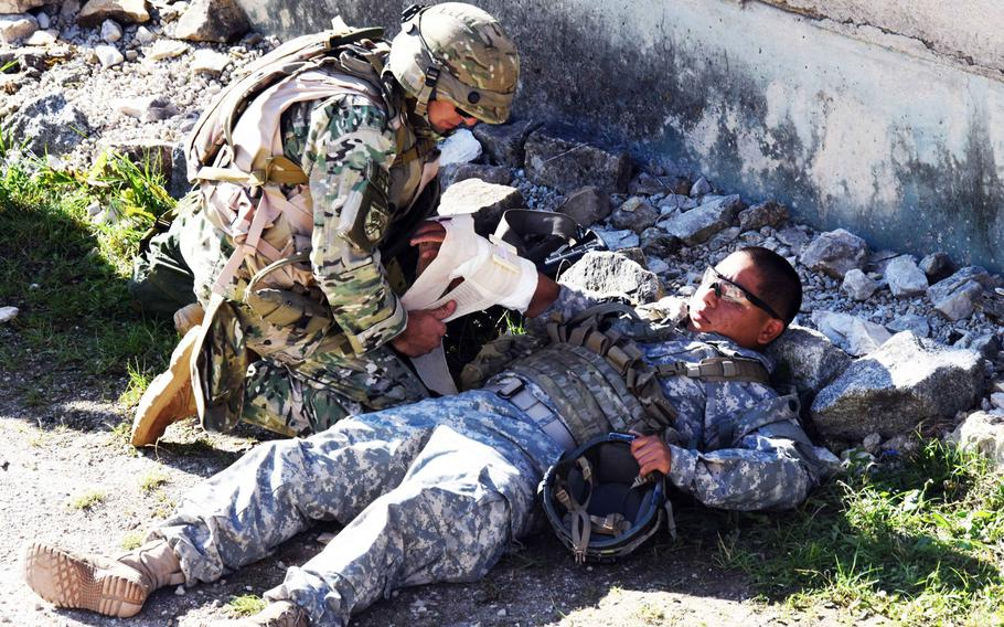 A Georgian soldier provides first aid to an American soldier during training in Hohenfels, Germany, Tuesday, Aug. 15, 2017. The 15-day mission rehearsal exercise, which ends on Aug. 22, is the final step to certifying the Georgian unit is ready to deploy with coalition forces in support of Operation Freedom Sentinel.