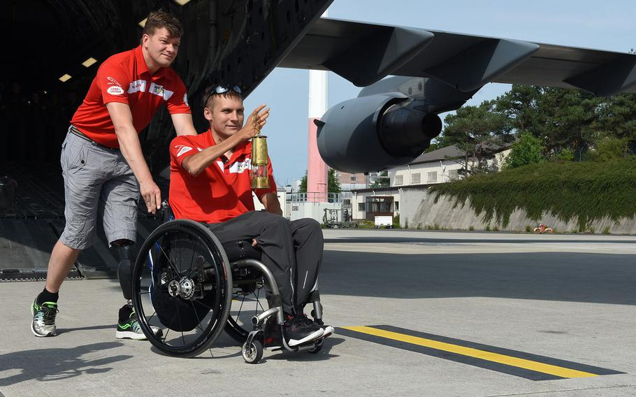 """Simon Mailloux, a major with Canadian Forces, pushes Chris Klodt, a former Canadian Forces soldier on Tuesday, Aug. 15, 2017, at Ramstein Air Base, Germany. Klodt carried a lit lantern to symbolize the """"spirit flame"""" for the upcoming Invictus Games next month in Toronto. Mailloux and Klodt were injured in Afghanistan."""