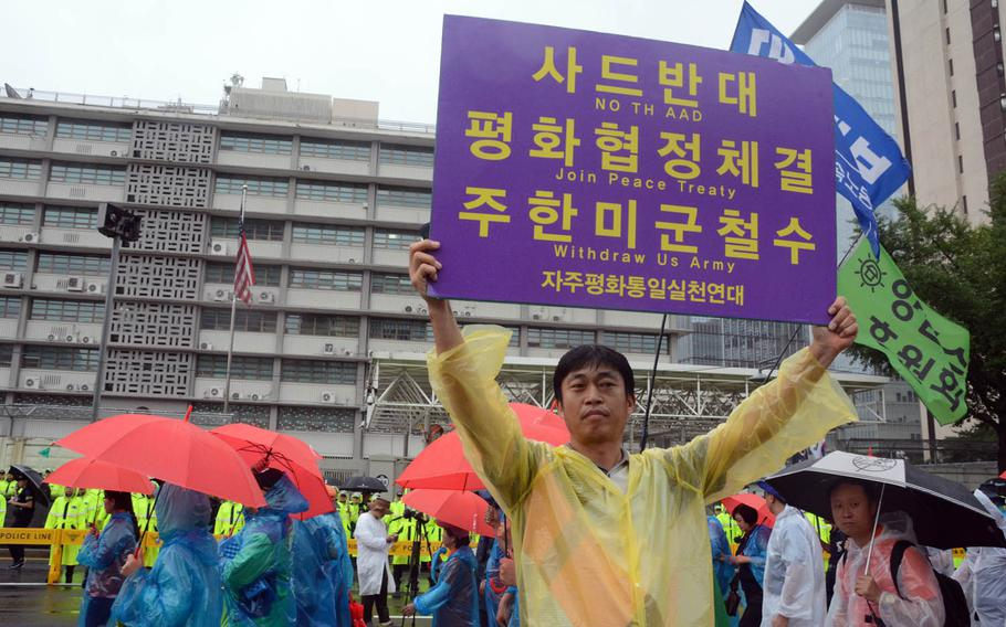 A man holds a sign during a South Korean protest in front of the U.S. Embassy in Seoul, Tuesday, Aug. 15, 2017. The sign called for the withdrawal of the U.S. Army, a peace treaty with North Korea and an end to the deployment of the advanced missile defense system known as THAAD.
