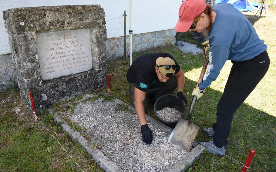 Joan Baker, an anthropologist, and Marine Corp. Julian Temblador remove small stones from the top of a grave next to a church in Pokojisce, Slovenia, on July 17, 2017. A team representing the Defense POW/MIA Accounting Agency conducted a mission in Slovenia in July to search for the remains of Sgt. Alfonso Duran, an airman missing since World War II.