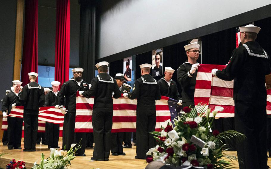 Sailors ceremonially fold seven American flags during a memorial ceremony on June 27, 2017, at Yokosuka Naval Base, Japan, for the USS Fitzgerald sailors who were killed in a collision at sea on June 17.