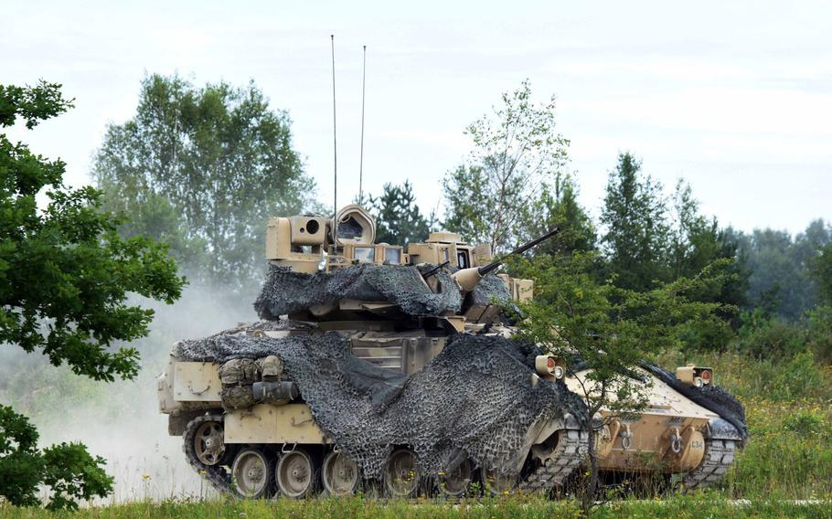 A Bradley Fighting Vehicle drives towards the a line of M1A2 Abrams tanks during a live fire exercise, Aug. 18, 2017, in Grafenwoehr, Germany.