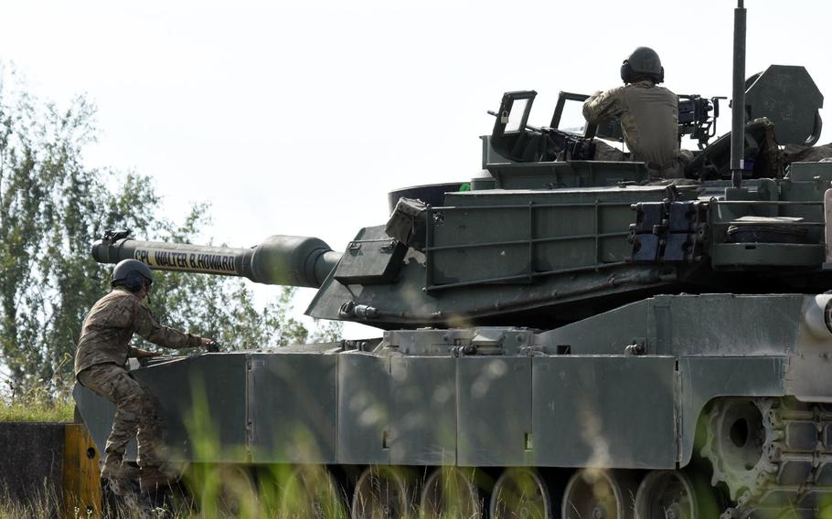 A U.S. Army tanker climbs on an M1A2 Abrams tank after a live fire exercise, Aug. 18, 2017, in Grafenwoehr, Germany.
