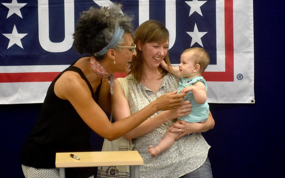 Celebrity chef Carla Hall shares a laugh with Kim and Eliana Portale during an autograph session Wednesday, Aug. 23, 2017, at the Army and Air Force Exchange Service store at Aviano Air Base, Italy.