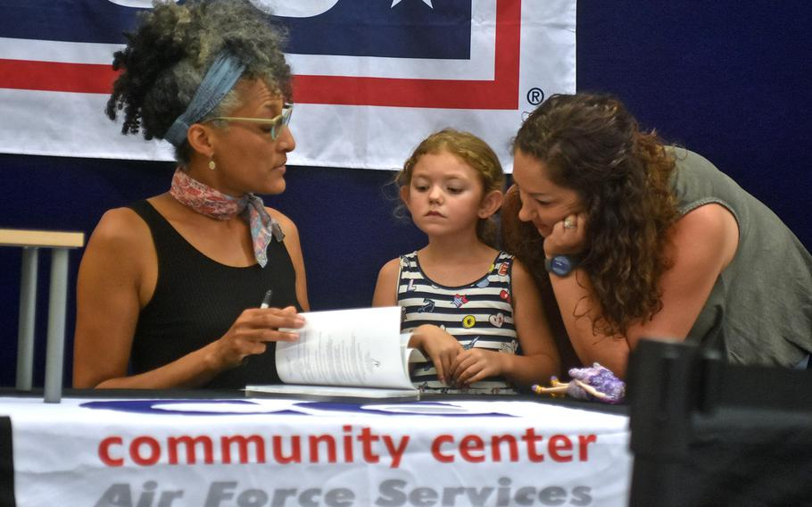 """5-year-old Olivia Kirchhofer and mother Danielle watch celebrity chef Carla Hall sign a book on Wednesday, Aug. 23, 2017, at the base exchange. Hall is on a three-base USO tour in Europe before resuming her co-host duties on """"The Chew' next week."""