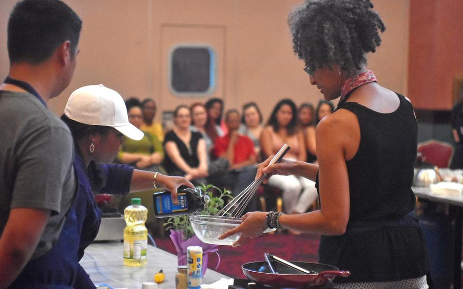 Celebrity chef Carla Hall gets some help from one of the cooks she's tutoring during a demonstration Wednesday, Aug. 23, 2017 at La Bella Vista Club at Aviano Air Base, Italy.