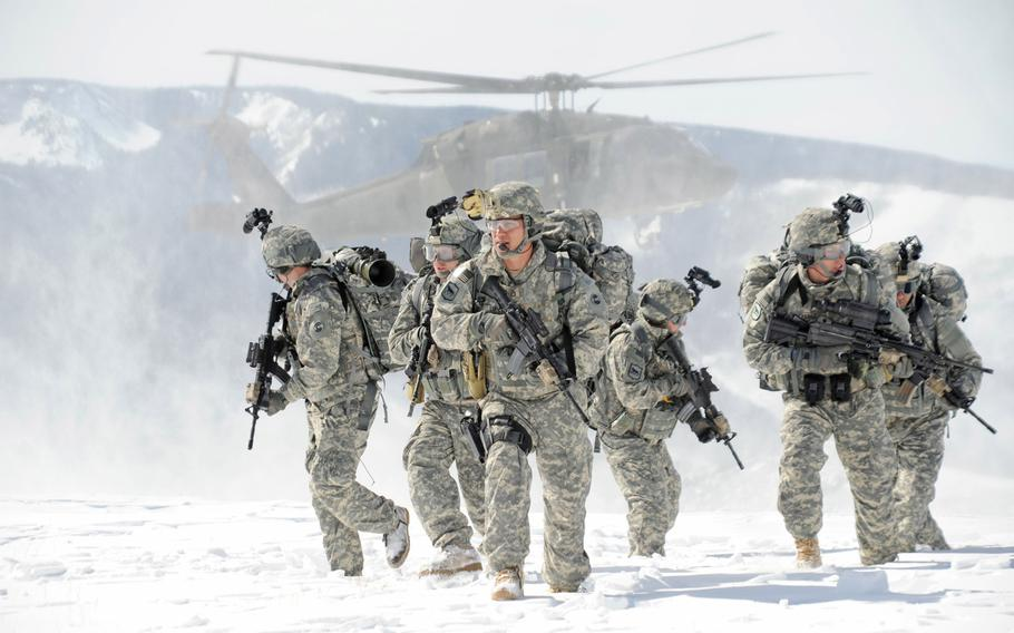 Soldiers wearing Extended Cold Weather Clothing System gear move through a snowy terrain after dismounting from a helicopter in March 2010. Army scientists are working with nanotechnology to produce cold-weather uniforms that will heat up when switched on and wick moisture away more efficiently.
