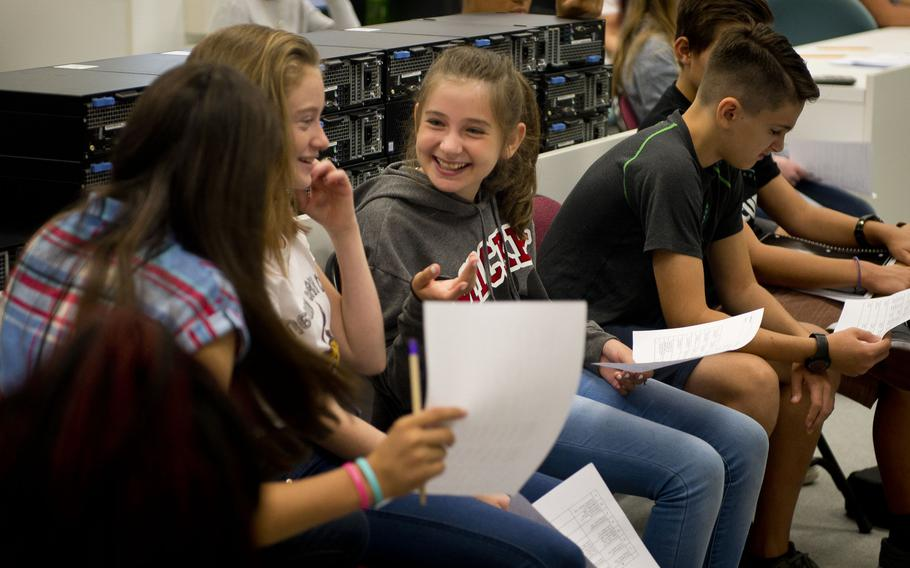 Seventh-grade students compare schedules during the first day of school at Kaiserslautern Middle School at Vogelweh, Germany, on Monday, Aug. 28, 2017.