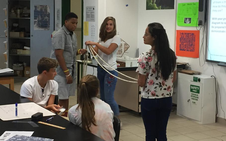 Geometry students use a rope to show how to calculate a triangle during their first day of classes, Monday, Aug.28, 2017, at Naples High School near Naples, Italy.