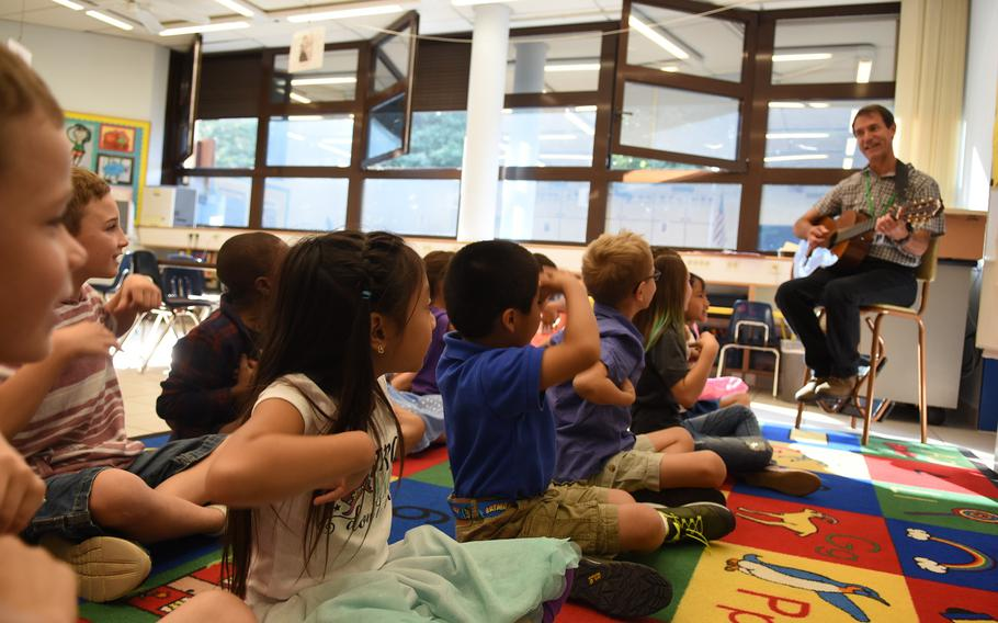 Second-graders at Ramstein Elementary School in Germany laugh and sing along while art teacher Jules Fritz plays some silly songs on the guitar at the end of art class on Monday, Aug. 28, 2017.