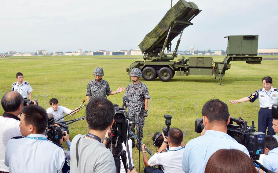 Japan Air Self-Defense Force personnel talk to reporters in front of a Patriot missile-defense system at Yokota Air Base, Japan, Tuesday, Aug. 29, 2017.