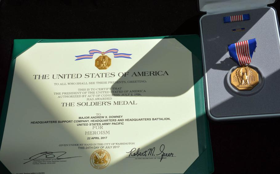 The Soldier's Medal and citation awarded to Maj. Andrew Downey at Tuesday, Aug. 29, 2017, at Fort Shafter, Hawaii, for rescuing a family of three from drowning off the shore of Kauai in April.