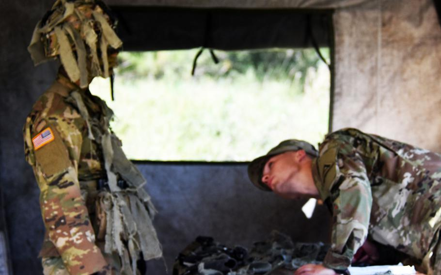 Spc. Jacob Henrikson, winner of the US Army Europe Best Warrior Challenge, inspects Pfc. Lucas Bria's camoflauge during Expert Infantry Badge certification at Hohenfels, Germany,  on Wednesday, Aug. 30, 2017.