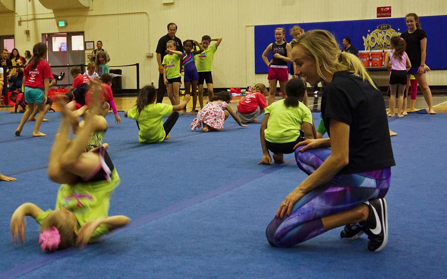 Nastia Liukin, all-around women's gymnastics champion and three-time silver medalist at the 2008 Summer Olympics, watches a child's successful forward roll during a youth gymnastics clinic at Yokota Air Base, Japan, Thursday, Aug. 30, 2017.