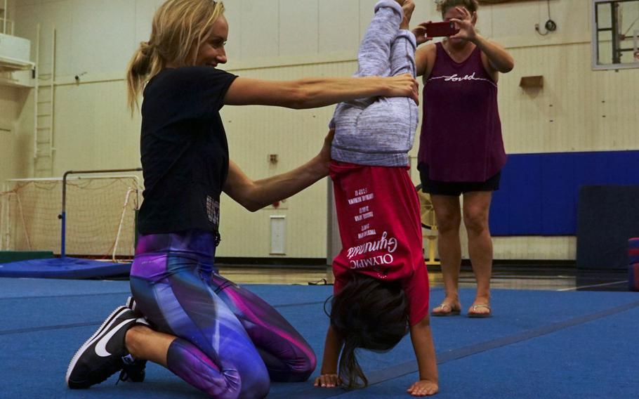 Nastia Liukin, all-around women's gymnastics champion and three-time silver medalist at the 2008 Summer Olympics, helps a child perform a handstand during a youth gymnastics clinic at Yokota Air Base, Japan, Thursday, Aug. 30, 2017.