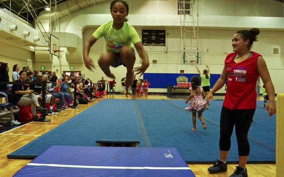 """Laurie Hernandez, a gold and silver medalist at the 2016 Summer Olympics and winner of the 23rd season of """"Dancing with the Stars,"""" watches a participant leap from a springboard during a youth gymnastics clinic at Yokota Air Base, Japan, Thursday, Aug. 30, 2017."""
