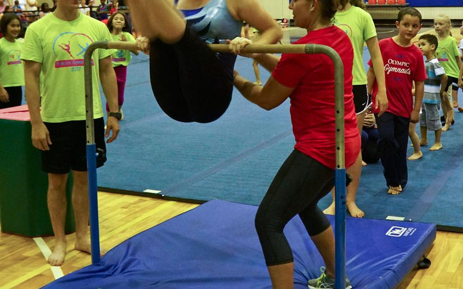 Desiree Sanchez, a 20-year veteran of USA Gymnastics who has previously worked alongside Olympic gold-medalists Shannon Miller and Dominique Moceanu, helps a gymnast spin on the bar during a youth gymnastics clinic at Yokota Air Base, Japan, Thursday, Aug. 30, 2017.