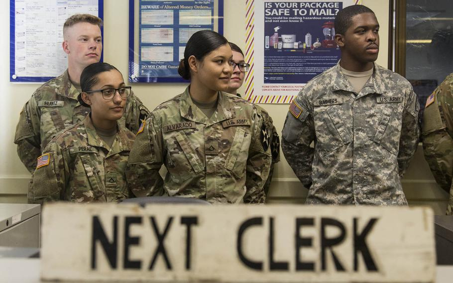 Mail clerks attend the unveiling of a postage cancellation stamp commemorating the 2nd Infantry Division's 100th anniversary at the Camp Red Cloud, South Korea, post office, Monday, Oct. 2, 2017.