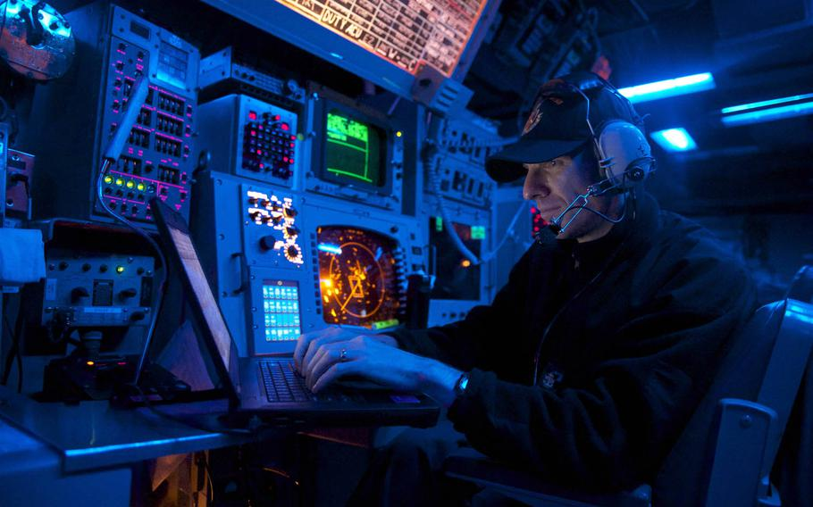 A sailor stands watch in the combat information center aboard the guided-missile destroyer USS John S. McCain as it sails east of the Korean Peninsula in 2014.