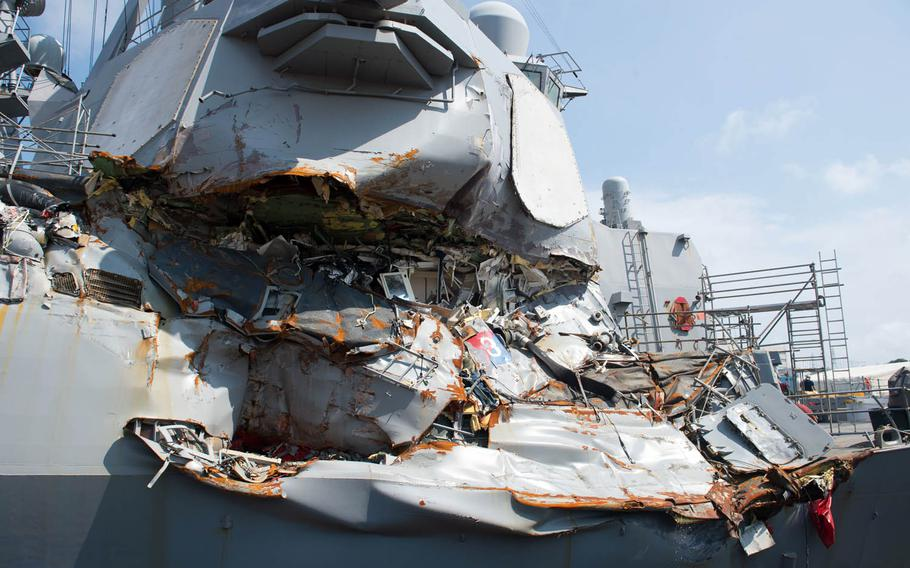 The guided-missile destroyer USS Fitzgerald sits in dry dock over the summer at Yokosuka Naval Base, Japan, to continue repairs and assess damage sustained from its June 17 collision with a merchant vessel. This view shows damage above the waterline to the outside skin of the ship.
