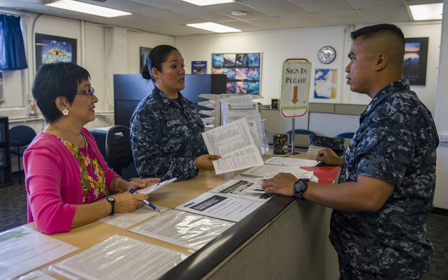Gwyen Nosse, director of Navy College Office Hawaii, left, and Cryptologic Technician 2nd Class 'Gabriela Carrillo, explain the tuition assistance process to Culinary Specialist 1st Class Maximino Salvador at Joint Base Pearl Harbor-Hickam, Hawaii, Aug. 15, 2017.